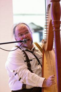 Andreas trägt Trachtenhemd und Lederhose und spielt Harfe und singt in ein Mikrophon.