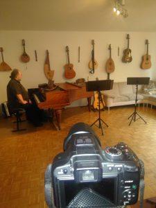 Der Blick über die Kamera auf Flügel mit Panflöte und Notenständer. Im Hintergrund hängen viele Gitarren an der Wand. Unser Wohnzimmer als Bühne...
