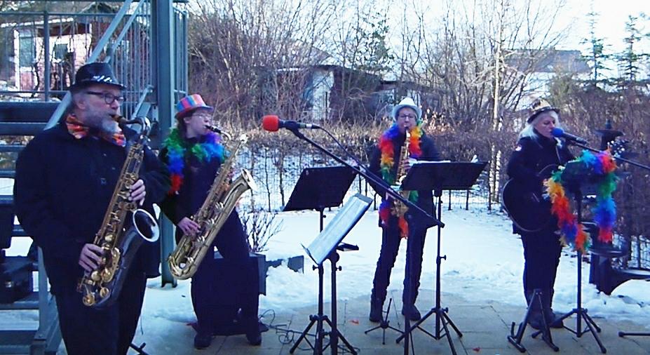 Vier Musiker mit Glitzerhüten und Regenbogenfarbenen Stolas stehen im Schnee und spielen auf verschiedenen Saxophonen und einer Gitarre .